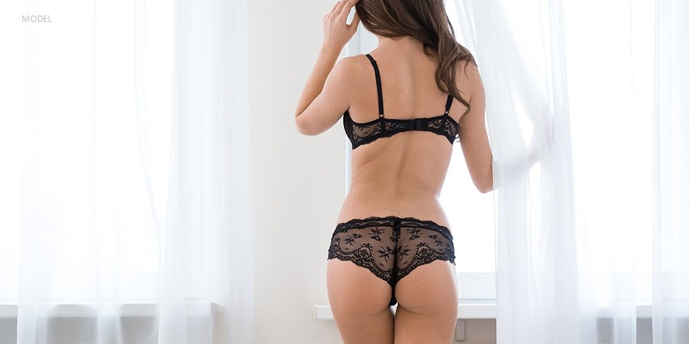 View of Curvy Woman's Lifted Buttock in Black Lingerie
